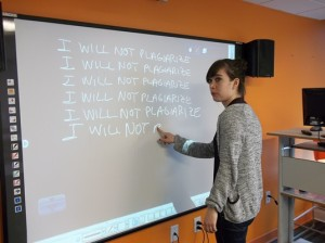 EC Academic Assistant Renee 'doing lines' on the board in a style borrowed from The Simpsons' theme song animation.