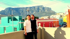 """Yank"" from Taiwan with his friend Murat from Turkey. The two friends are standing in the historical and colourful area of Bo Kaap with a stunning backdrop of Table Mountain"