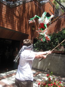 EC San Diego's current youngest student swings at the pinata.