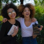 two women holding books in a park