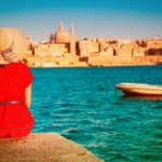 mulher estudando inglês em Malta, sentado em Sliema, observando a vista de Valletta